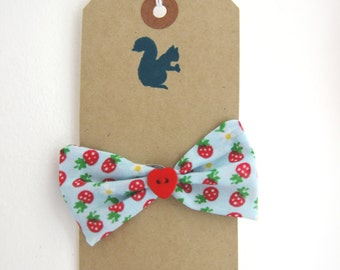 Strawberry and Daisy print on a pale blue bow with a central red heart button on a snap barette clip.