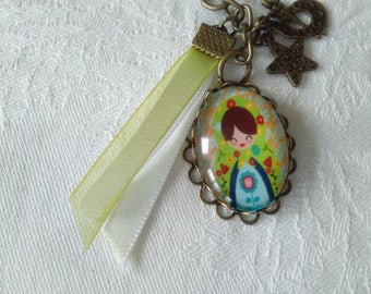 key ring with cabochon glass doll, bronze charms star, satin and organza Ribbon and color scheme