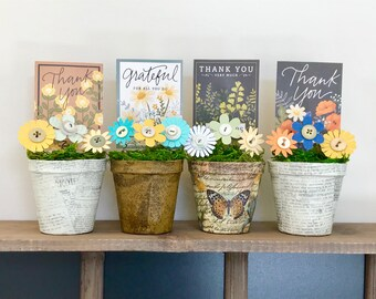 Peat pots with flowers and cheerful 'Thank you' message