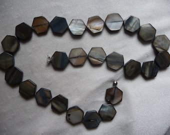 Beads, Mother of Pearl, 15mm Hexagon, Shades of Gray.  Sold per 16 inch strand. There are 26 beads on the strand.