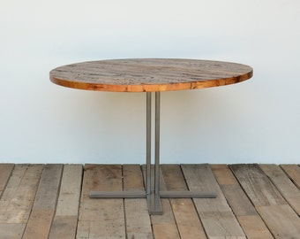 Round pedestal dining table in reclaimed wood and steel legs in your choice of color, size and finish.  Custom inquiries welcome.