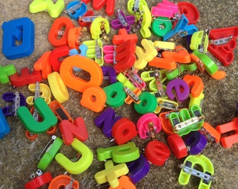 Alphabet letter badges in a rainbow of colours,red,blue,green,yellow,orange,pink,purple.Get your initial or spell a word out.Great fun gift!