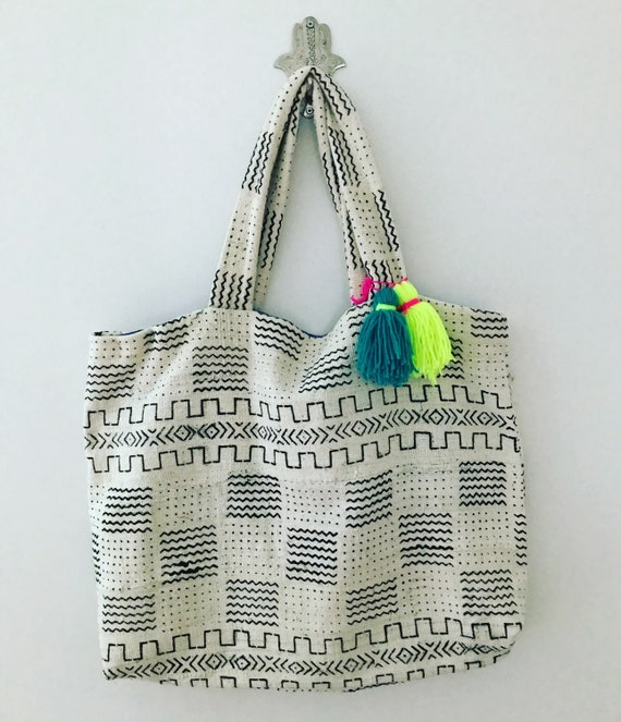 Oversized extra large tote bag holdall shopper in white and black Mali Mud Cloth finished with neon yellow, turquoise tassel Pom Pom