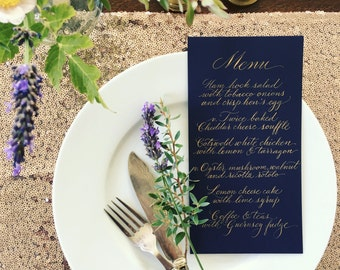 Elegant calligraphy wedding menus  in gold ink on midnight blue card