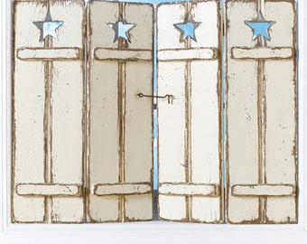 Distressed wooden shutters with traditional star cutout in creamy white