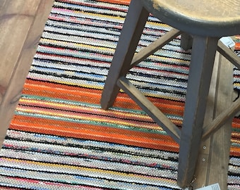 Orange yellow green black striped floor runner rug. Decorative and practical. High traffic and pet friendly. Traditional Scandinavian rug.
