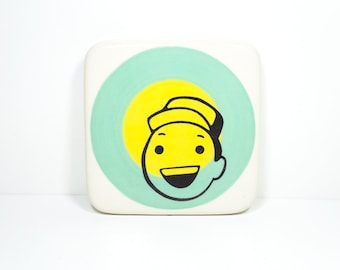 """tile with a dude we think is saying """"Hey!"""" on colour block of blue green and yellow, made to order."""