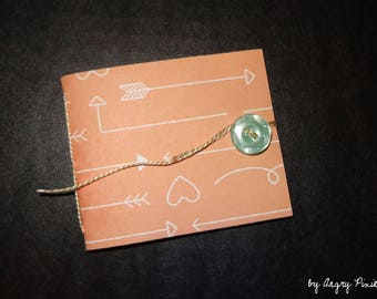 Little pink handmade notebook pattern hearts and arrows with blue button