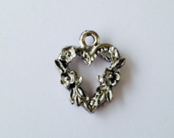 Flowered heart pewter charm in  silver finish.   Package of 12.  All of our charms are at or below wholesale prices.Made in USA.