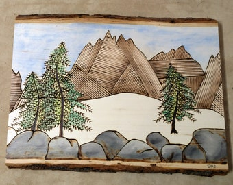 """The """"Snow In The Mountains"""" is a Hand-drawn Wood Burned Watercolor of the Mountains with Snow in the Foreground"""