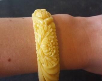 Stunning primrose yellow bakelite bangle engraved with flowers.