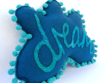 Dream Cushion No. 12 - A super cute and unique felt cloud pillow in teal with turquoise writing and turquoise pom pom trim. Dream pillow