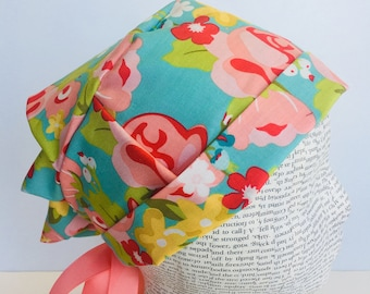 Ribbon Tie Back Scrub Cap scrub hat with a light blue material with flowers in pink and green with a matching ribbon