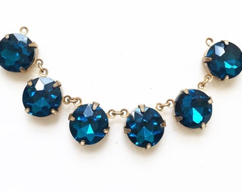 round navy blue acrylic gem cut round rhinestones set in gold tone metal salvaged chain of cabochon connectors