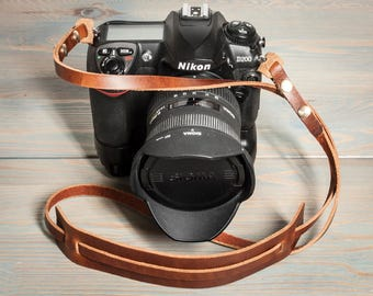 Hand made leather universal camera strap. Chestnut or Tan with brass Chicago screws and shoulder pad.