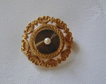 Neat little gold tone brooch in with a pearl in the centre