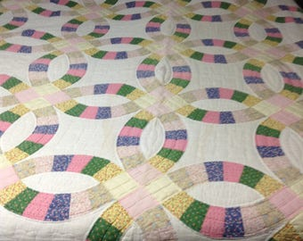 Vintage mid-century hand-stitched quilt in wedding ring pattern.