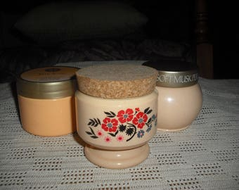 There are three jars consisting of 2 cream sachets and a candle.