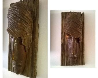 Unique, handmade, ceramic face sculpture on driftwood