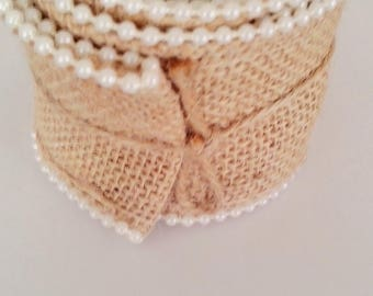 Roll of beige burlap and pearls