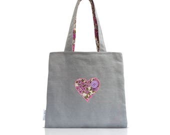A unique tote shoulder bag with heart, button and stitching detail.