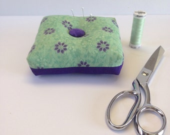 Square, box style Pincushion with a green and purple floral print