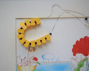 Choker necklace with yellow plastic cubes and black glass beads