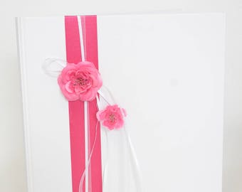 White guest book and ribbons, flowers