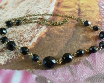 Black multifacetted beads of various dimensions on antique bronze chain