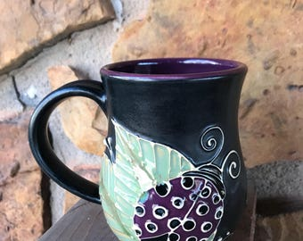 Lady Bug mug handmade thrown pottery slip trailed Purple and black w/green leaves