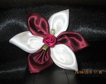 White and Burgundy satin with a flower is adorned with a transparent white button with in the Middle a white flower