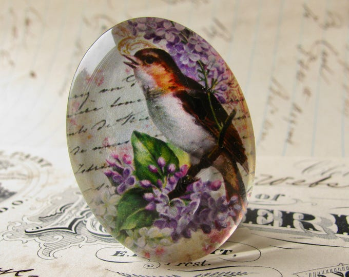 Songbird perched on lilac, from our Beautiful Birds collection of handmade glass cabochons, 40x30mm, purple flower, script background
