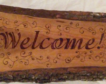 Welcome, wood burned sign with curling scrolls and shapes on cherry wood.