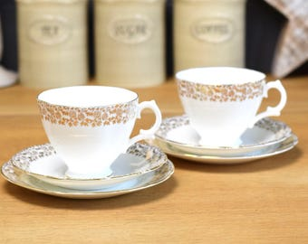 Pair of white and gold cup, saucer and plate trios, white and gold bone china from Royal Stuart (England)