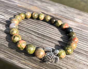 Genuine jasper bracelet. 8 mm beads. Silver turtle detail. Natural colours.
