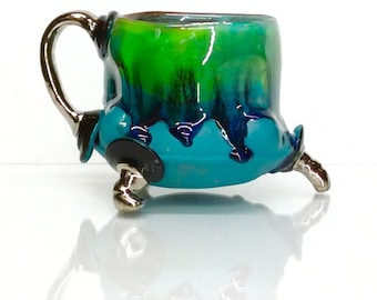 drippy glaze turquoise green mug with black and white gold accents with two finger handle