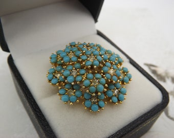 A fine Sphinx round flower head vintage jewelry brooch made in openwork goldtone metal set with turquoise & sparkly clear white glass stones