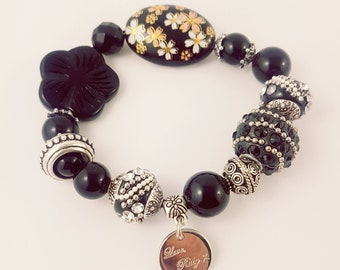 Black and silver bracelet featuring onyx, kashmiri beads and pressed glass.