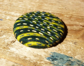 Badge embroidered in green and yellow African fabric