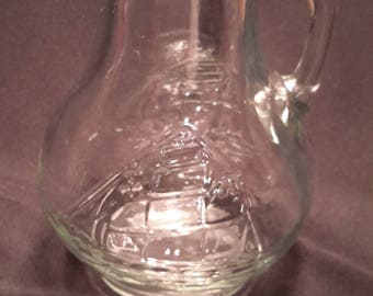 Pitcher with embossed sailboat made of glass