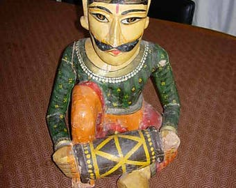 carved and hand painted indian man playing a drum