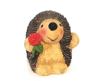 The cutest little hedgehog holding a flower