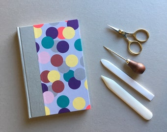 Hand bound A5 notebook journal quarter bound with grey book cloth and decorative spotty paper bookbinding