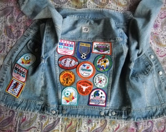 Collectible denim jacket embellished with 14 embroidered soccer patches.  Size Large, by Best World