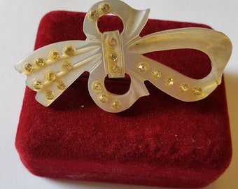 Vintage hand carved mother of pearl bow brooch.