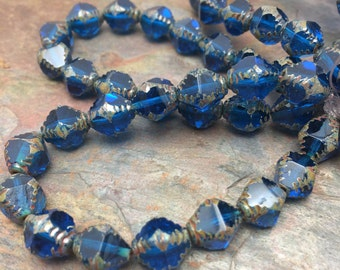 Czech Pressed 10x08mm Bicone Beads. 15 beads. Color: Transparent Capri blue with picasso finish.