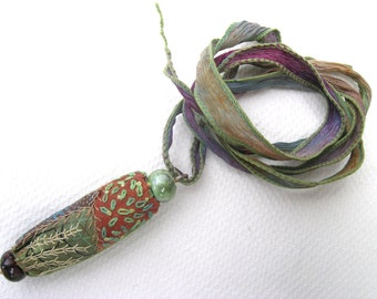A unique hand crafted hand made embroidered beaded crazy silk patchwork pendant in greens and browns with hand dyed ribbon