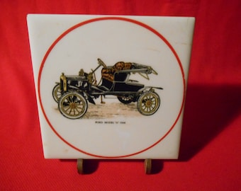 """One (1), 6"""" Square, Ceramic Tile Trivet, from Hyalyn, Depicting a 1906 Ford, Model N Auto, w/Wooden Stand."""