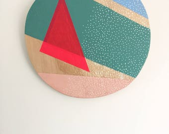 Neon pink geometric pattern painting on plywood circle