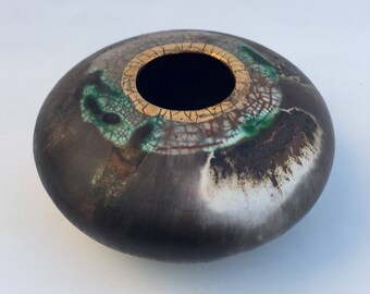 Smoke-fired ceramic pot. Porcelain vessel with gold lustre.
